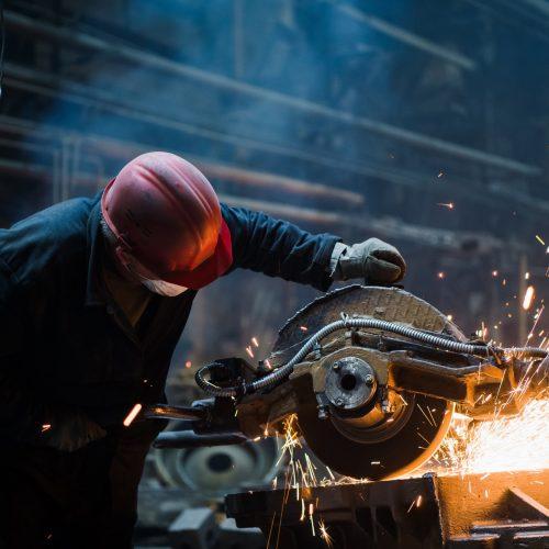 Employee grinding steel with sparks - focus on grinder. Steel factory